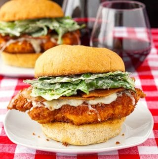 Panko Chicken Caesar Burgers square cropped feature image shown with burgers plus 2 glasses of wine in the background