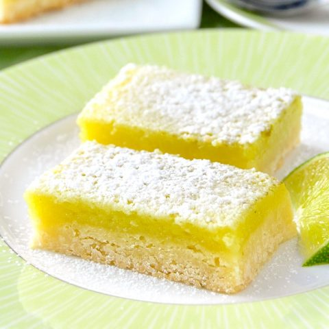 Super Easy Lime Bars with lime wedge on a green and white plate