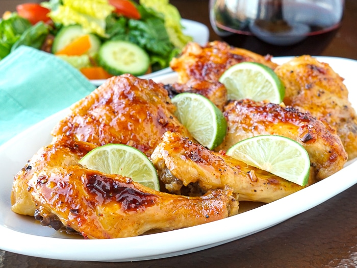 Sweet Chili Lime Chicken on a serving platter with wine and salad in background