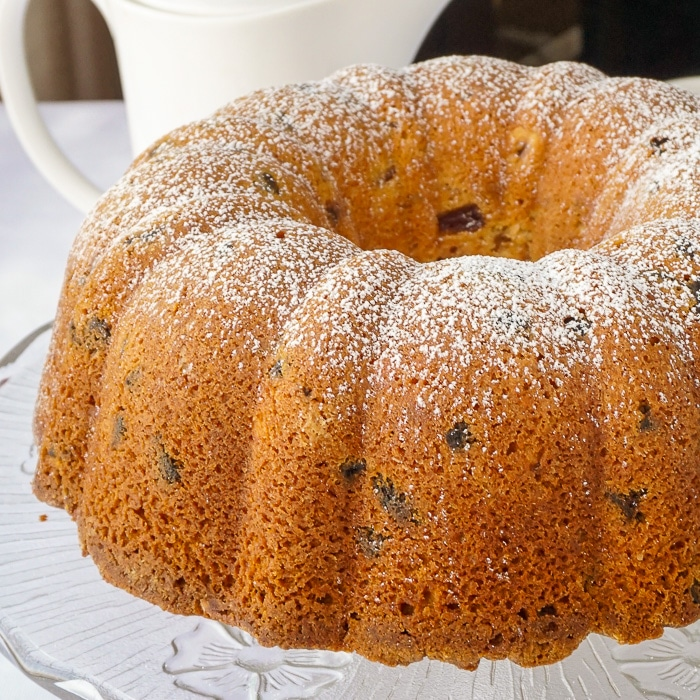 Uncut Apricot Hazelnut Pound Cake on a glass serving plate