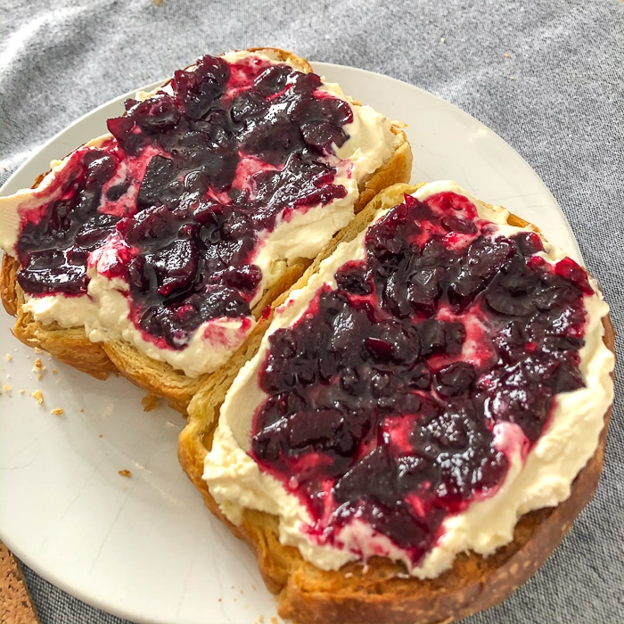 White bread with jam and cream on a white plate.