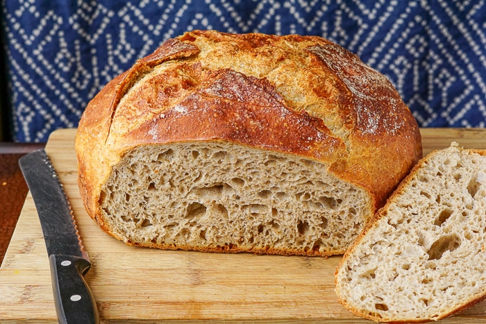 Whole wheat no knead bread on a wooden cutting board