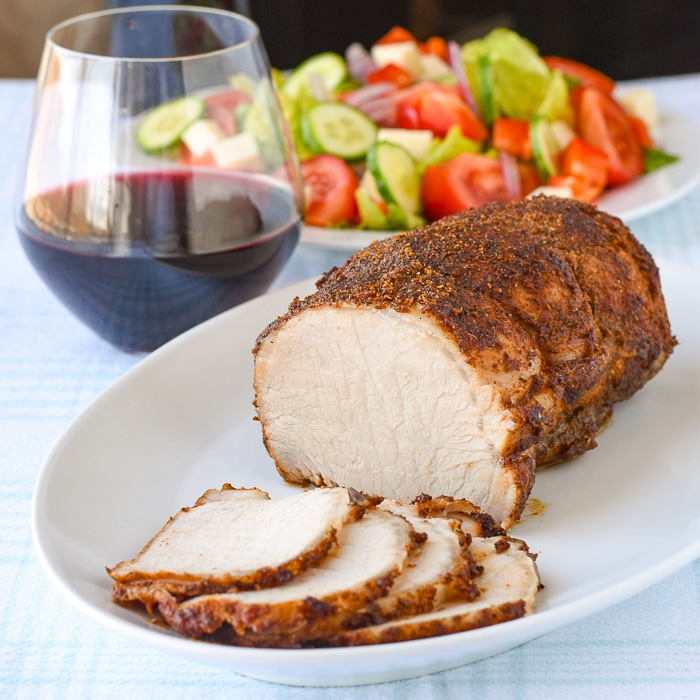 Brined Roast Pork Loin on a white platter with salad and wine in background