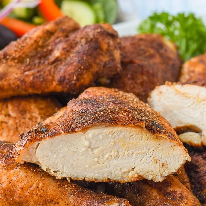 Copycat KFC Roast Chicken close up photo of a chicken breast sliced in half to show juicy interior