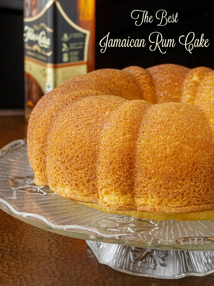 Jamaican Rum Cake on a glass pedestal stand with title text added for Pinterest
