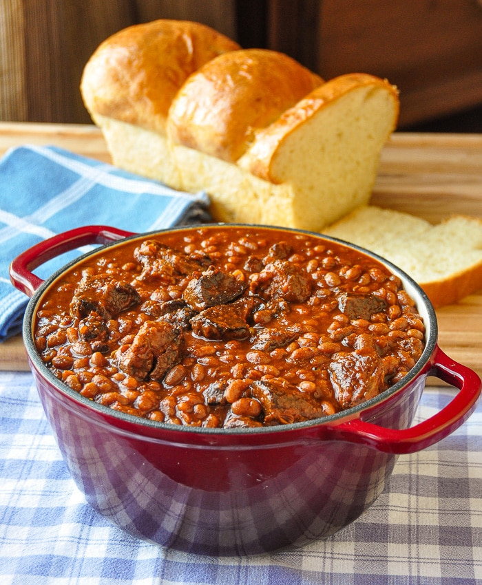 Maple Chipotle Pulled Pork and Beans in a red dutch oven with fresh baked bread in background