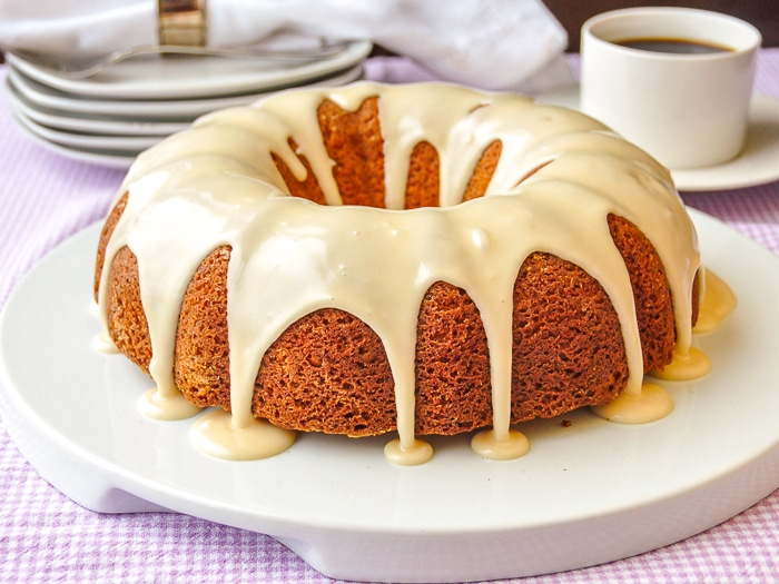 Maple Vanilla Bean Bundt Cake photo of uncut cake on with coffee service in the background