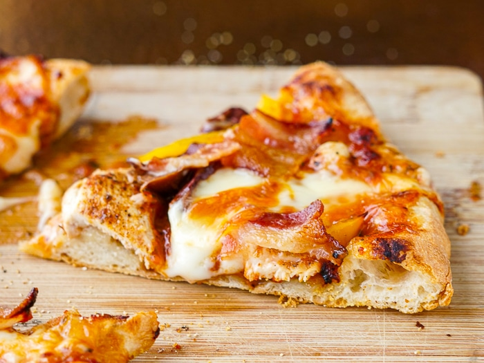!lose up photo of a slice of BBQ Chicken pizza