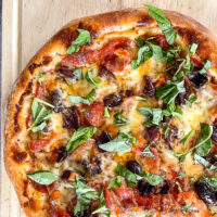Prosciutto and Pepperoni pizza close up photo.