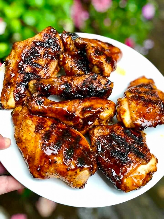 Honey BBQ chicken pieces on a white plate.
