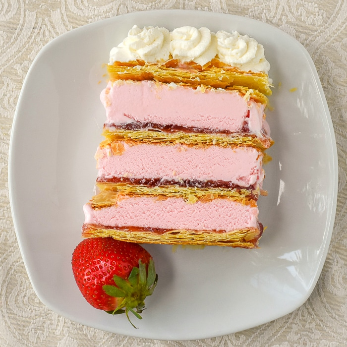 Strawberry Mille Feuille Ice Cream Cake photo of a single slice with a strawberry garnish on a white plate