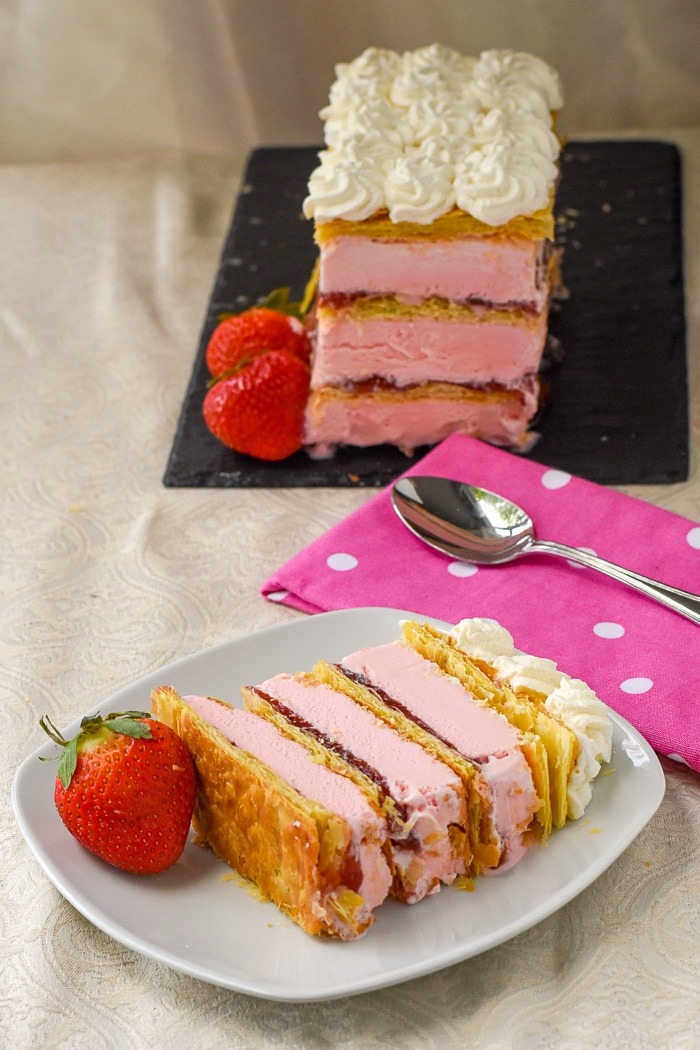 Strawberry Mille Feuille Ice Cream Cake photo of one serving with entire cake in the background
