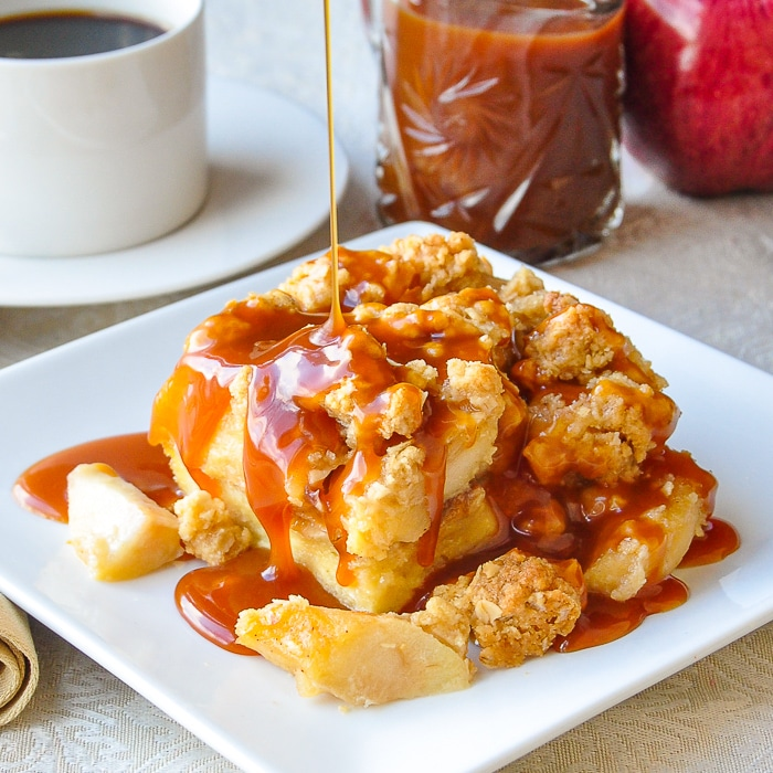 Apple Crumble Bread Pudding on a white plate with caramel, apple and coffee in the background