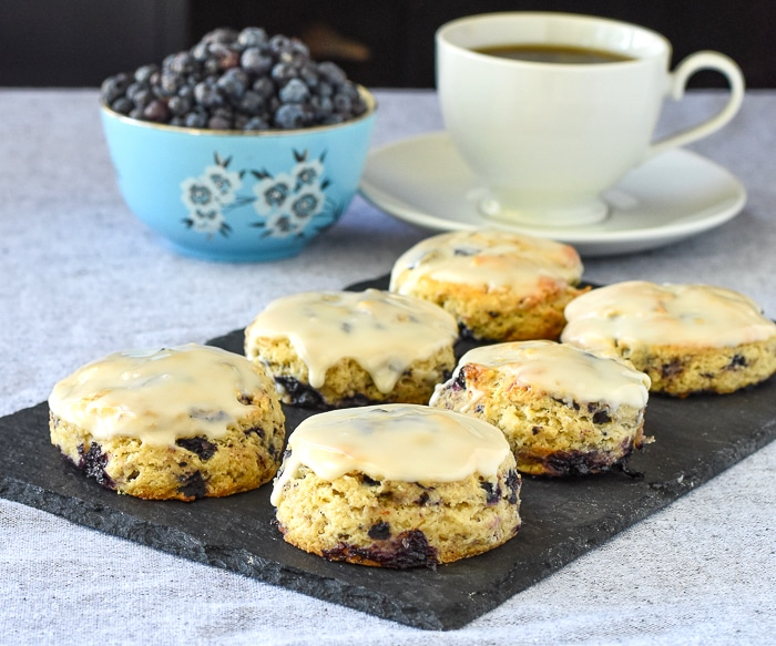 Blueberry Tea Buns on a slate serving plate with a bowl of blueberries and a cup of tea in the background