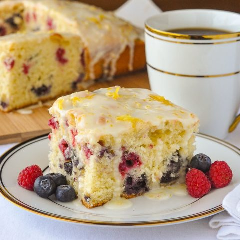 photo of a single slice of Lemon Drizzle Cake with Blueberries and Raspberries shown on a white and gold tea service