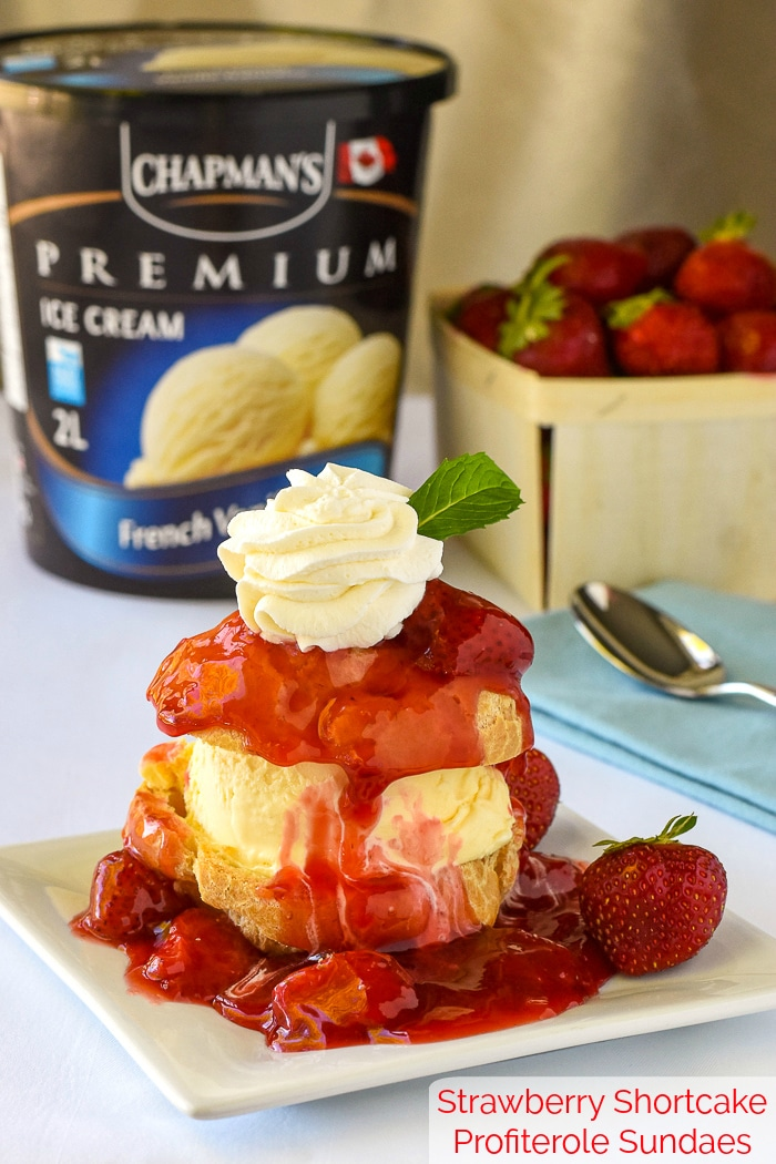 Strawberry Shortcake Profiterole Sundaes with strawberries and Chapman's French Vanilla ice cream in the background and title text added at bottom for Pinterest