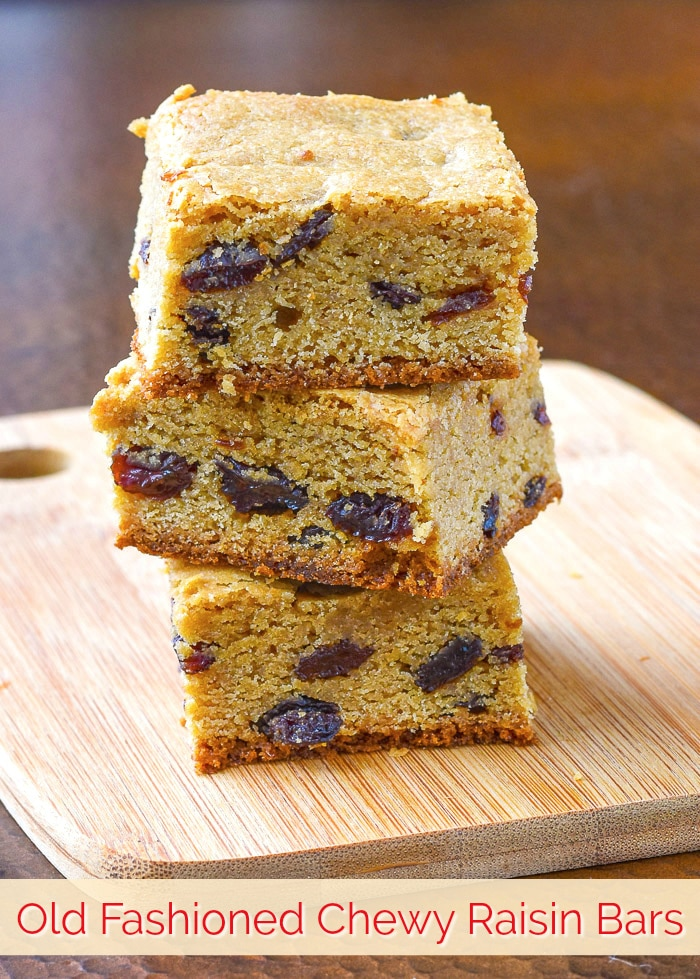 Chewy Raisin Bars stacked on a wooden cutting board with title text added for Pinterest