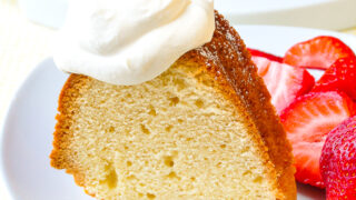 Close up photo of a singe slice of the Best Vanilla Pound Cake recipe shown with strawberries and whipped cream