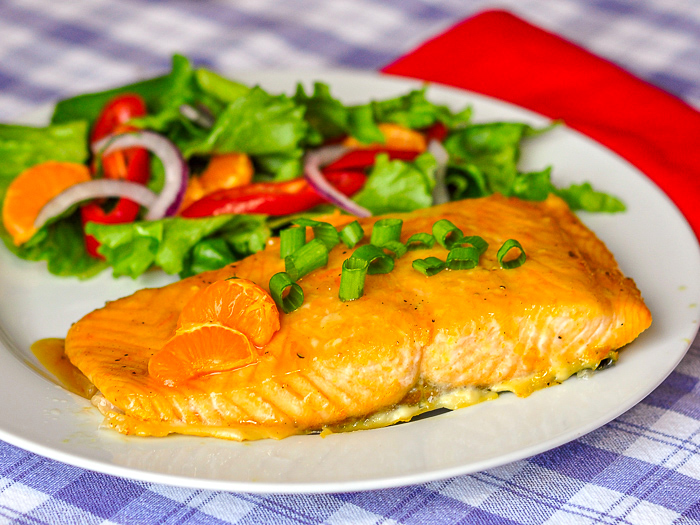 Ginger Orange Glazed Salmon shown with a mixed salad on a white plate.