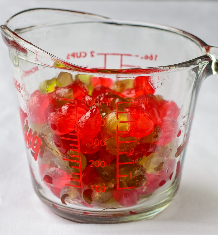 Red and green glace cherries in a clear glass measuring cup