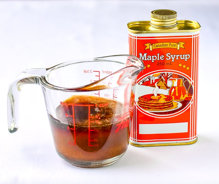 Simmered maple syrup in a glass measuring cup beside a can of maple syrup