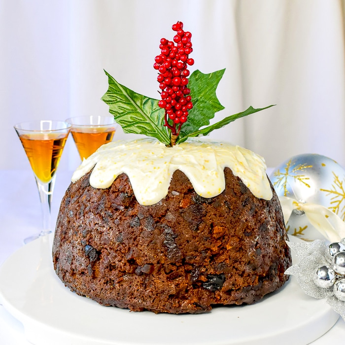 Christmas Plum Pudding with glasses of brandy and Christmas decorations on a white serving platter