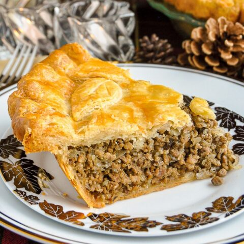 Christmas Tourtière slice shown on a white and gold plate copy