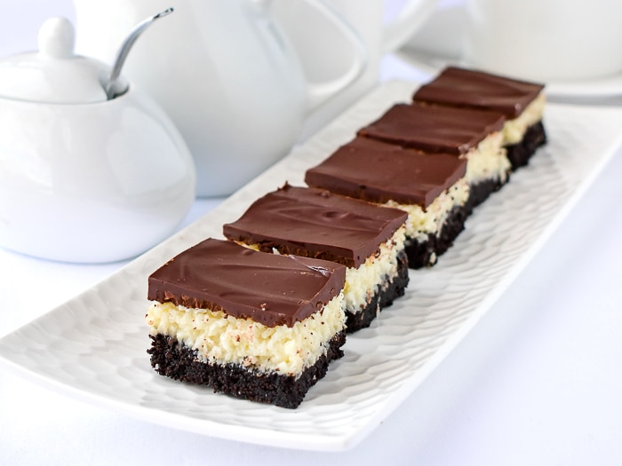 Coconut Bounty Cookie Bars on a white platter with coffee service in the background