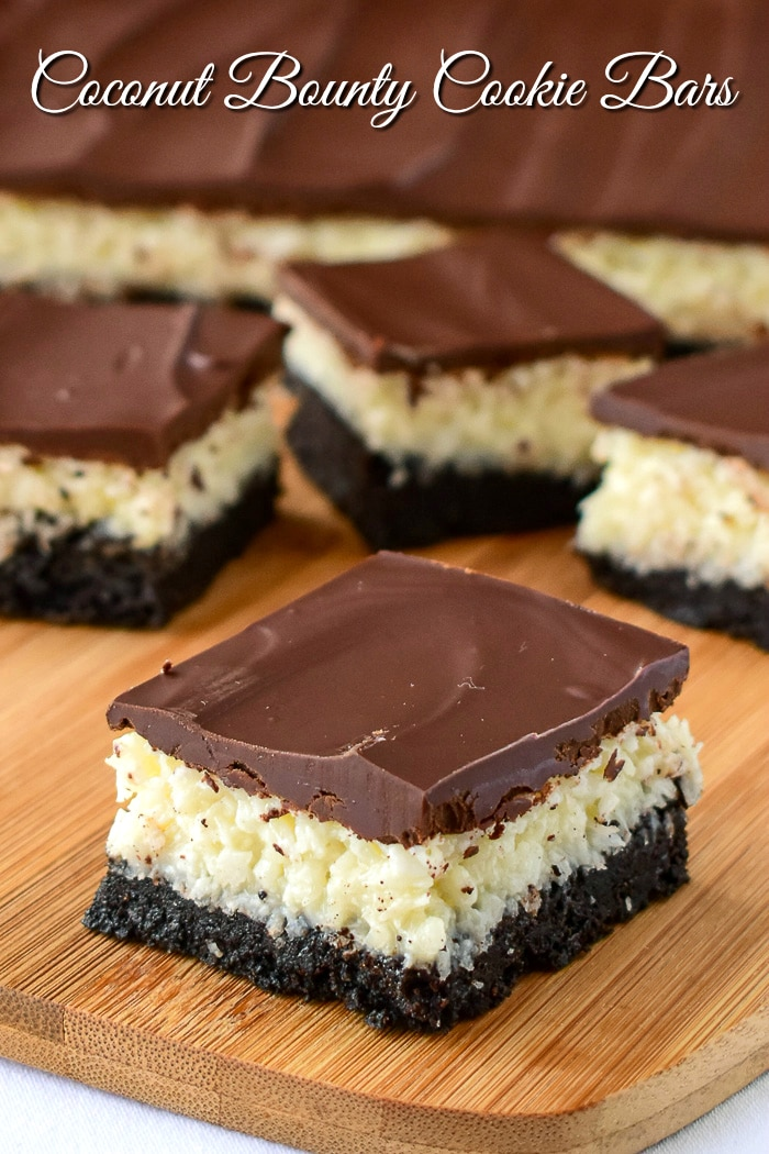 Coconut Bounty Cookie Bars photo of bars being cut on a wooden board with title text added for Pinterest