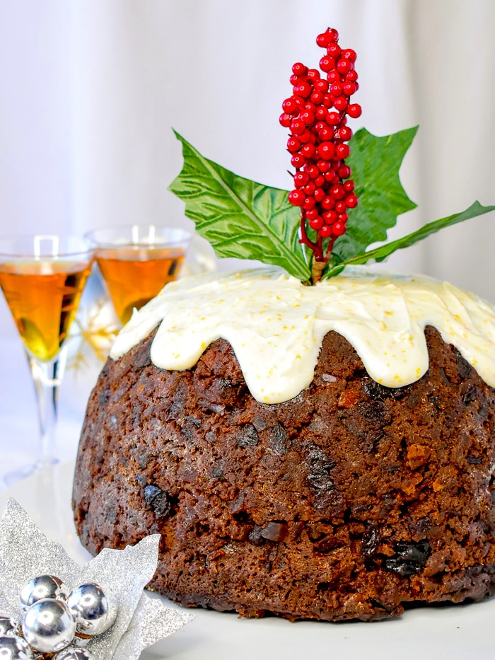 Completed Christmas Plum Pudding surrounded by Christmas decorations with a sprig of holly inserted in the top