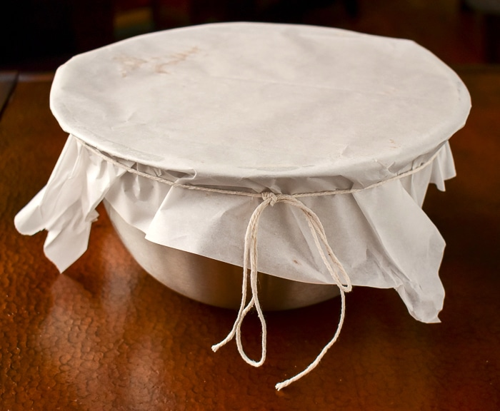 Cover the pudding bowl with a couple of layers of parchment paper and tie with butcher string
