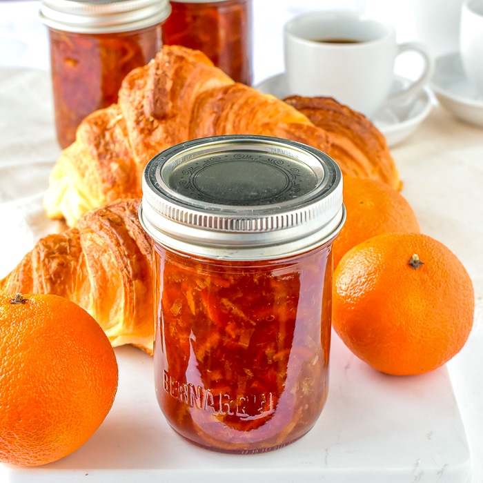 One jar of clementine marmalade pictured with croissants and fresh clemntines