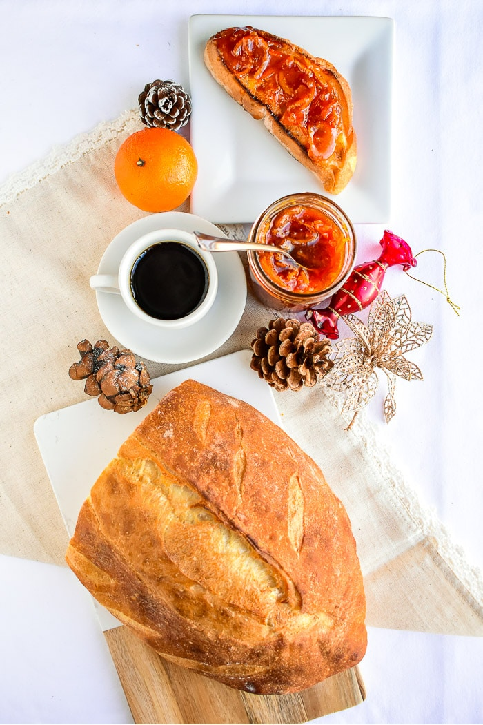 Overhead photo of marmalade, bread and christmas decorations all on a white tablecloth