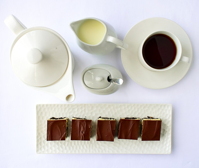 Overhead shot of Coconut Bounty Cookie Bars shown with a white coffee service