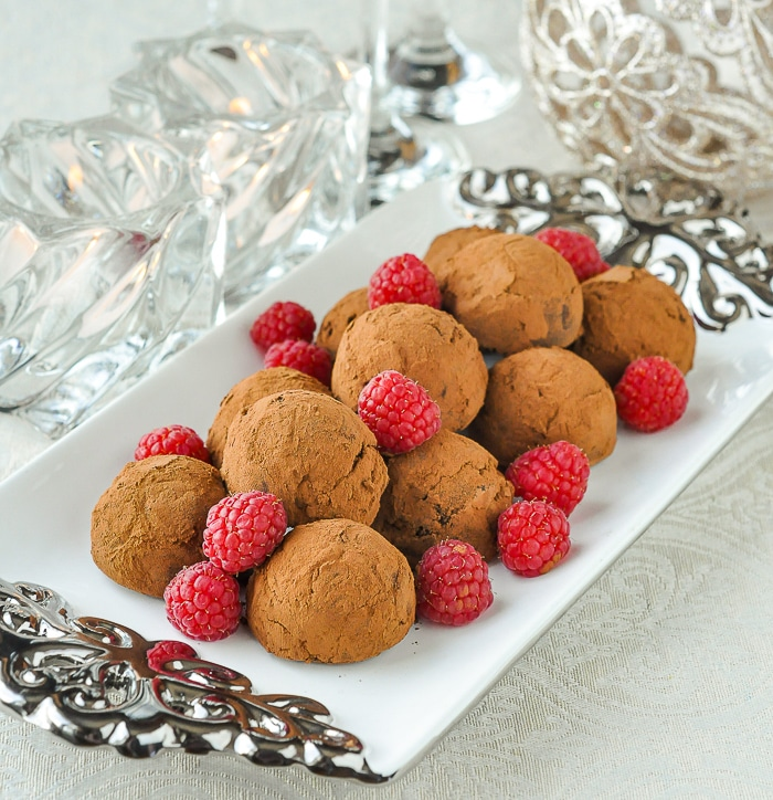 Raspberry Chocolate Truffles on a white and silver platter with candles and Christmas decorations in the background