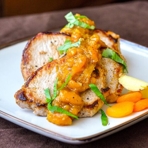Apricot Ginger Chutney on Pan Seared Pork Chops shown on a square ceramic serving platter