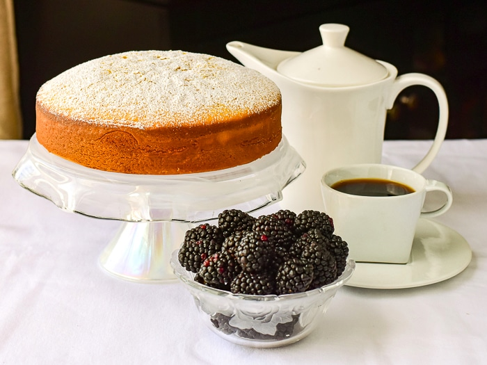 Condensed Milk Cake shown uncut with a white coffee service and blackberries