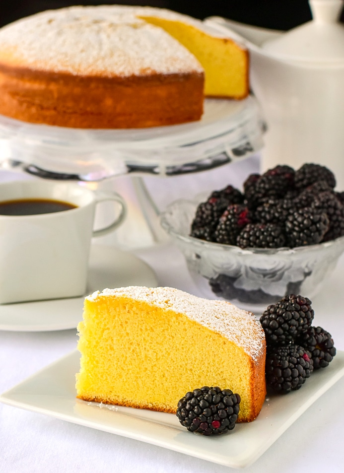 One slice of Condensed Milk Cake with blackberries coffee and a cake pedestal in the background