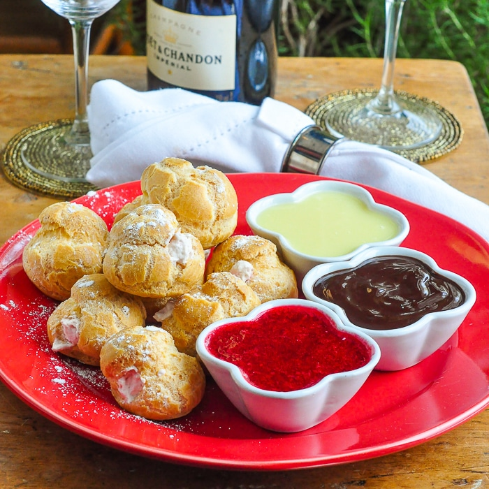 Raspberry Cream Profiteroles shown on a red plate with small ramekins of dipping sauces