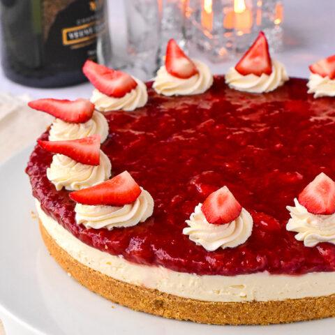 No Bake Strawberry Cheesecake garnished with whipped cream and fresh berries