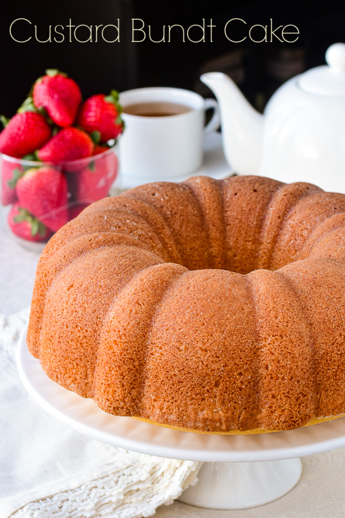 Photo of uncut Custard Bundt Cake on a white cake stand with strawberries and a tea service