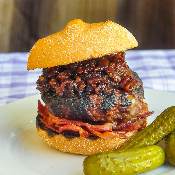 White Cheddar Burgers with beer and bacon jam photo on a white plate with pickles