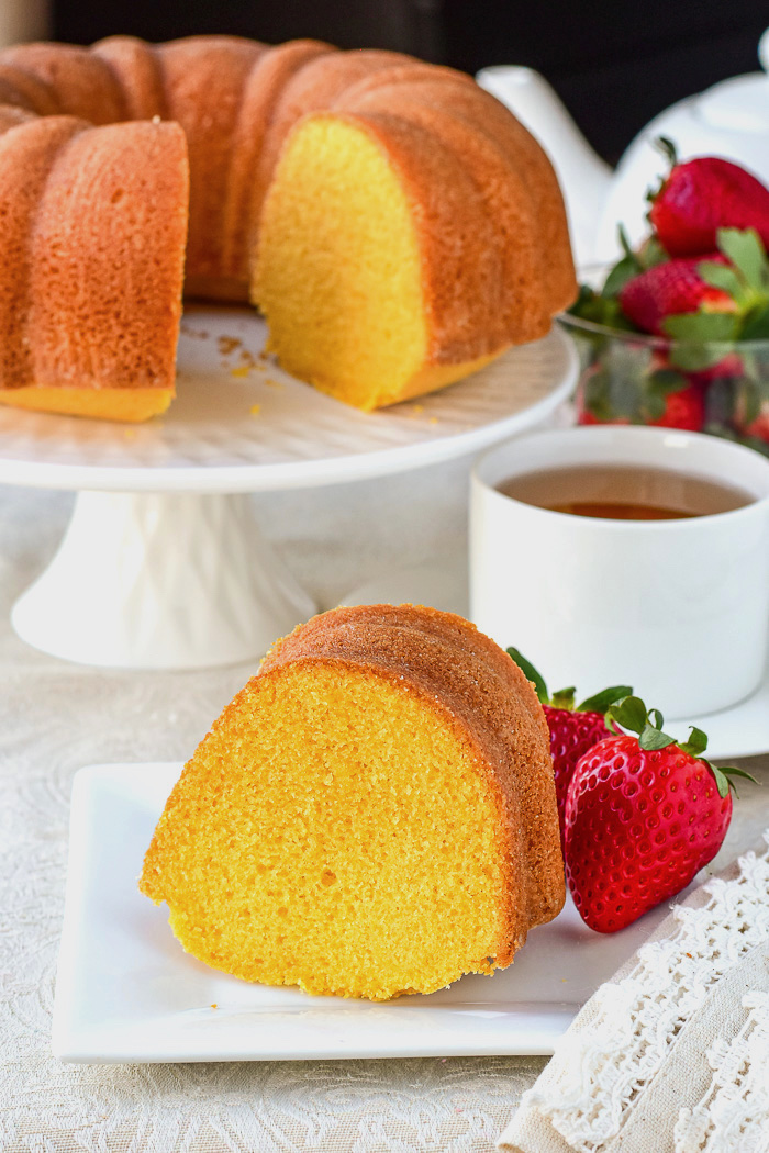 Wide shot photo of a single slice of custard bundt cake with full cake in the background