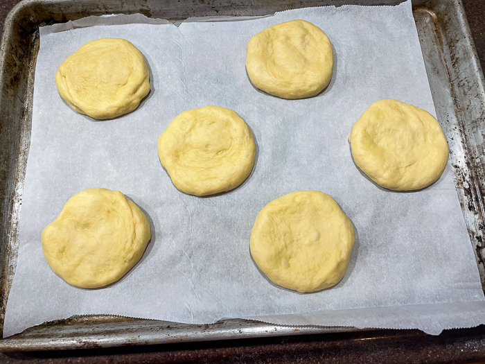 How to make the best hamburger buns photo showing buns with final stretch on a parchment lined baking sheet