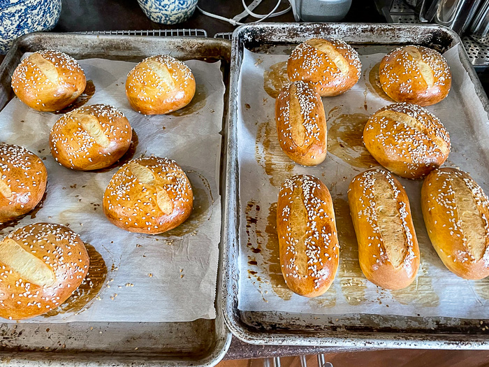 How to make the best hamburger buns recipe photo showing a completed batch of buns out of the oven that have been scored with a razor blade