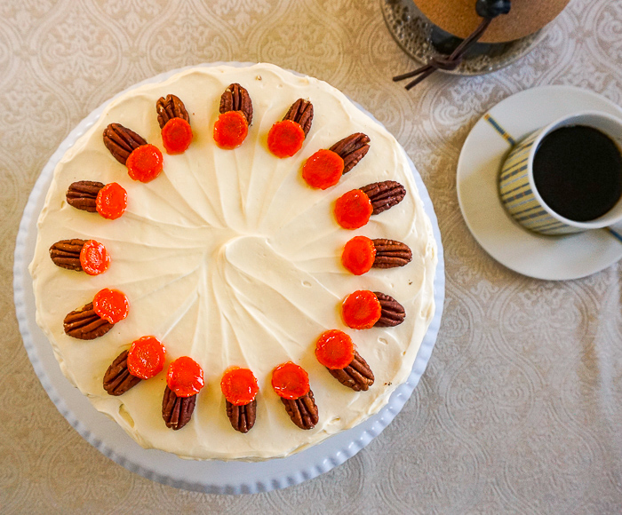 Overhead shot of an uncut carrot cake with coffee