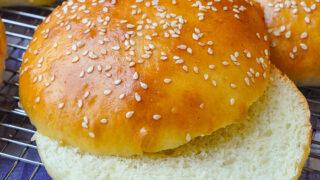 The Best Hamburger Buns Recipe close up photo of one bun split in half horizontally